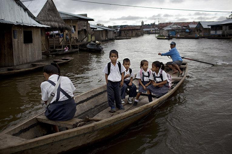 Перуанские ученики в городе Икитос плывут в школу по Амазонке
