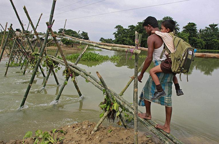Временный мост через реку, построенный после наводнения в деревне Бурхабурхи в Индии