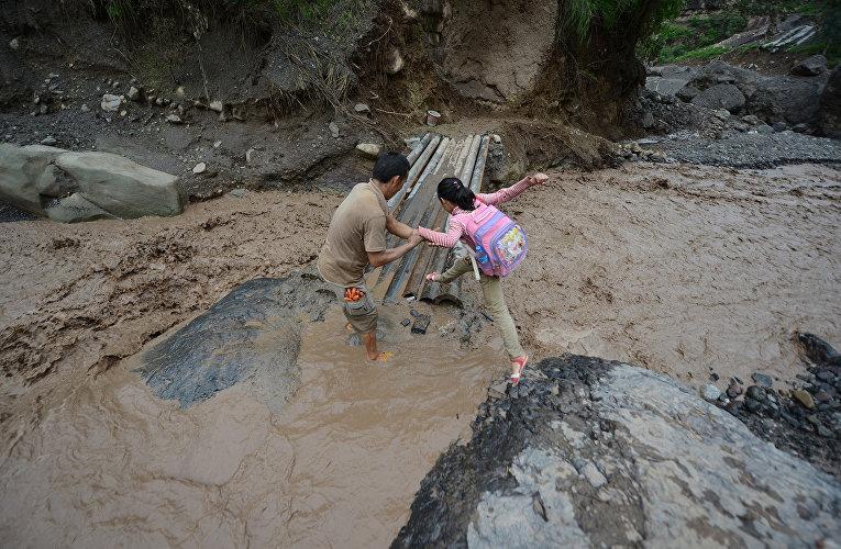 Девочка преодолевает грязевой оползень на пути в школу в китайской провинции Сычуань