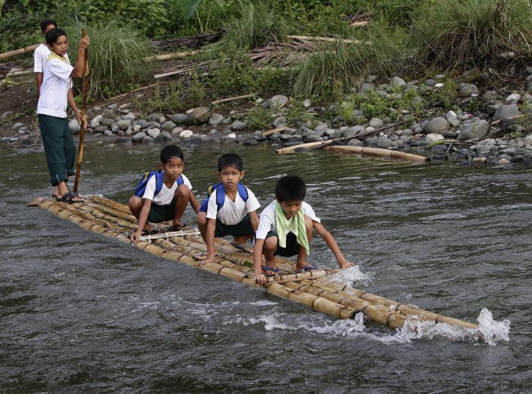 Филиппинские школьники плывут в школу на самодельном плоту