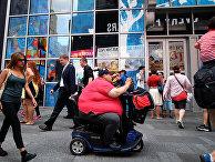 Мужчина с ожирением на электрическом самокате в Нью-Йорке