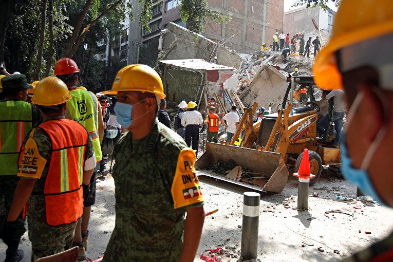 Солдаты и добровольцы работают на месте разрушенного землетрясением здания в Мехико