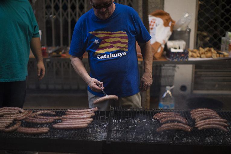 Мужчина жарит сосиски в Национальный день Каталонии в Барселоне