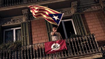 Мужчина держит флаг в поддержку независимости Каталонии в Барселоне