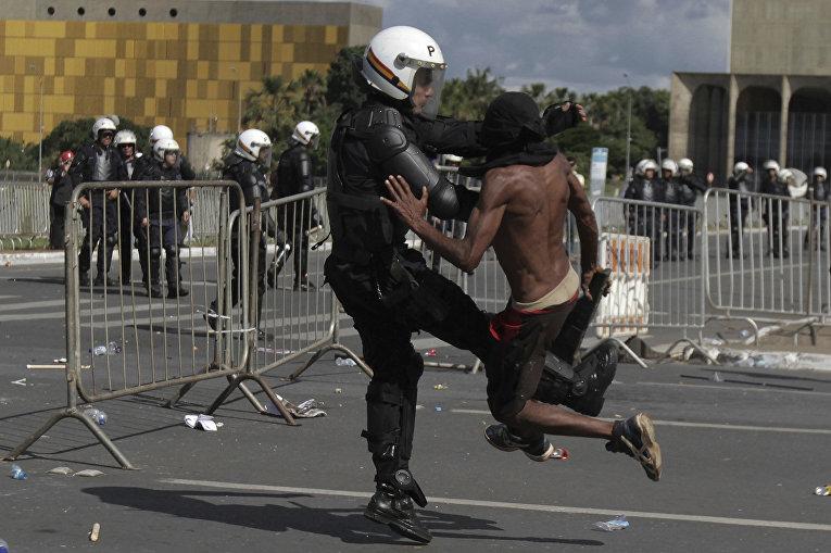 Столкновение демонстранта с полицией во время антиправительственного протеста в Бразилии