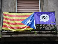 Агитационный плакат и флаг на одном из балконов в Барселоне, где проходит референдум о независимости Каталонии от Испании. 1 октября 2017
