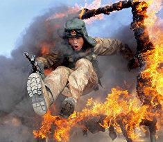 Солдат выполняет прыжок через горящее кольцо во время тактических учений в провинции Хэйхэ
