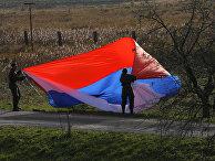 Сербские солдаты разворачивают российских флаг во время совместных с Россией антитеррористических учений