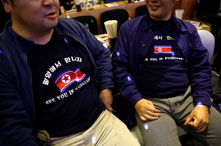 Фанаты Северной Кореи в тематических футболках на мероприятии