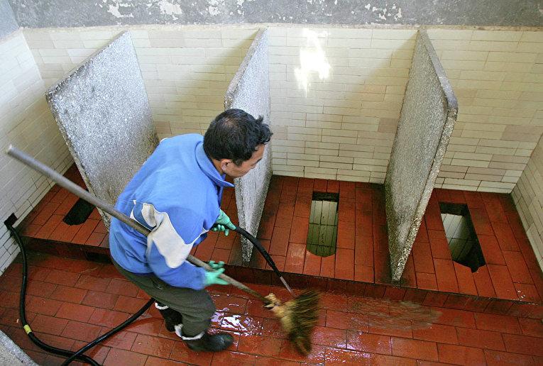 Работник очищает общественный туалет в Китае