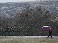 Местный житель с флагом и российские военные рядом с украинской военной базой в деревне Перевальное под Симферополем, 2 марта 2014 года