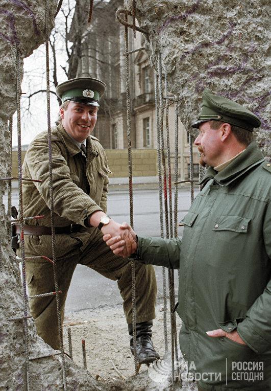 Пограничник из ГДР и полицейский из ФРГ обмениваются рукопожатием