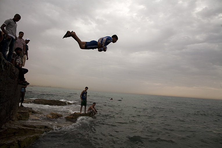 Местные жители спасаются от жары в море в Бенгази, Ливия