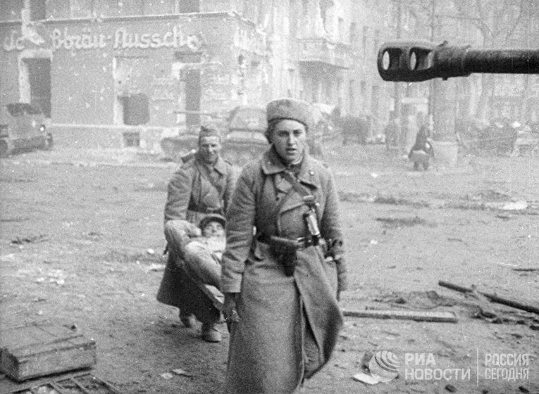 Женщина-санинструктор и санитар выносят на носилках раненого бойца