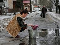Женщина в Донецке набирает воду из лужи